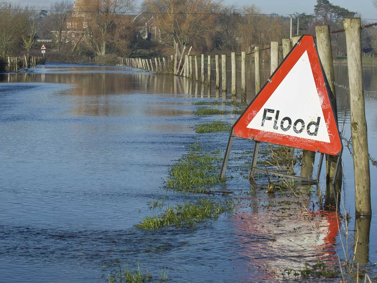 Flooded road with warning traffic sign