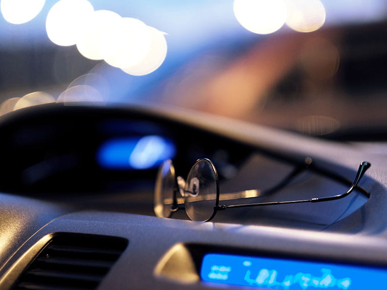 A pair of glasses resting on a dashboard to represent a driver's vision