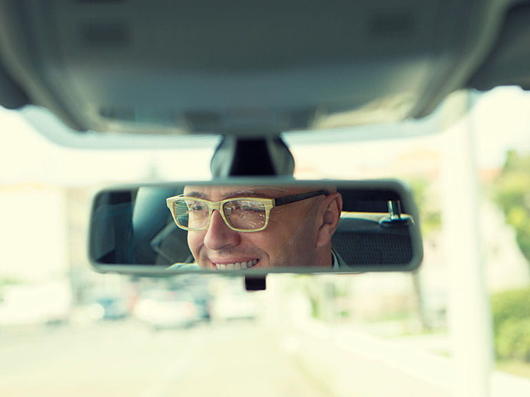 A man drives wearing his glasses as he is a responsible driver