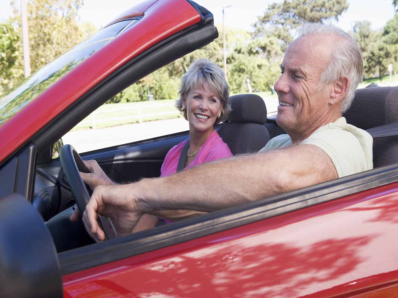 Mature couple driving a sportscar