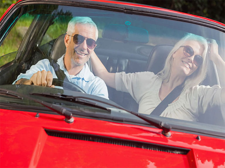 Mature couple driving a sportscar, having renewed their driving licences at 70