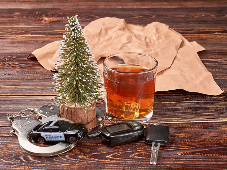 A whiskey glass sits next to some car keys to represent drink driving