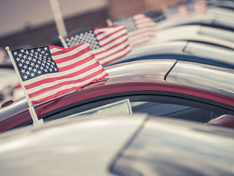 A row of American flags adorning American cars to represent hiring a car in America