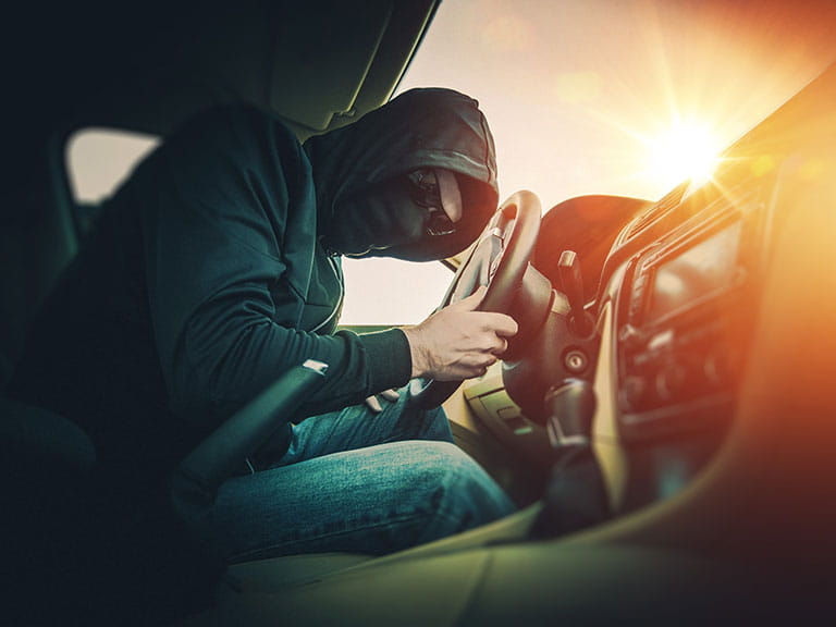A thief breaking into a car to steal the owner's valuable items
