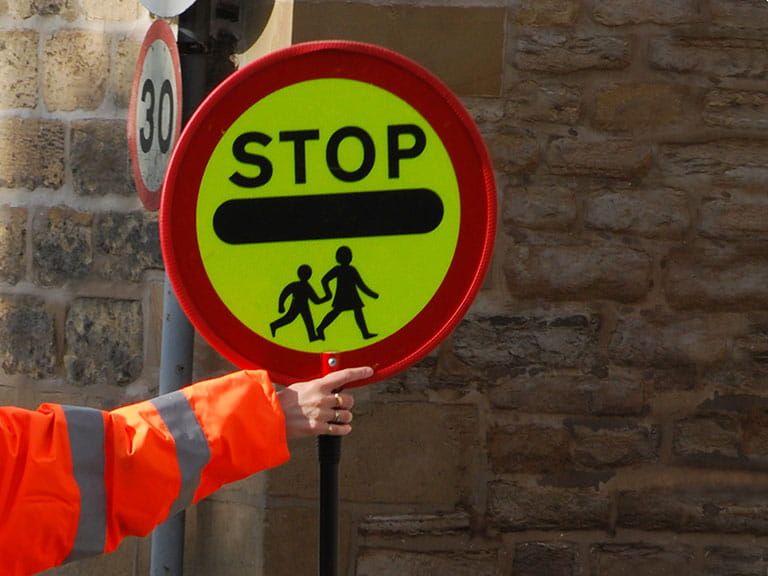 An arm of a lollipop person holding out the stop sign at a school crossing