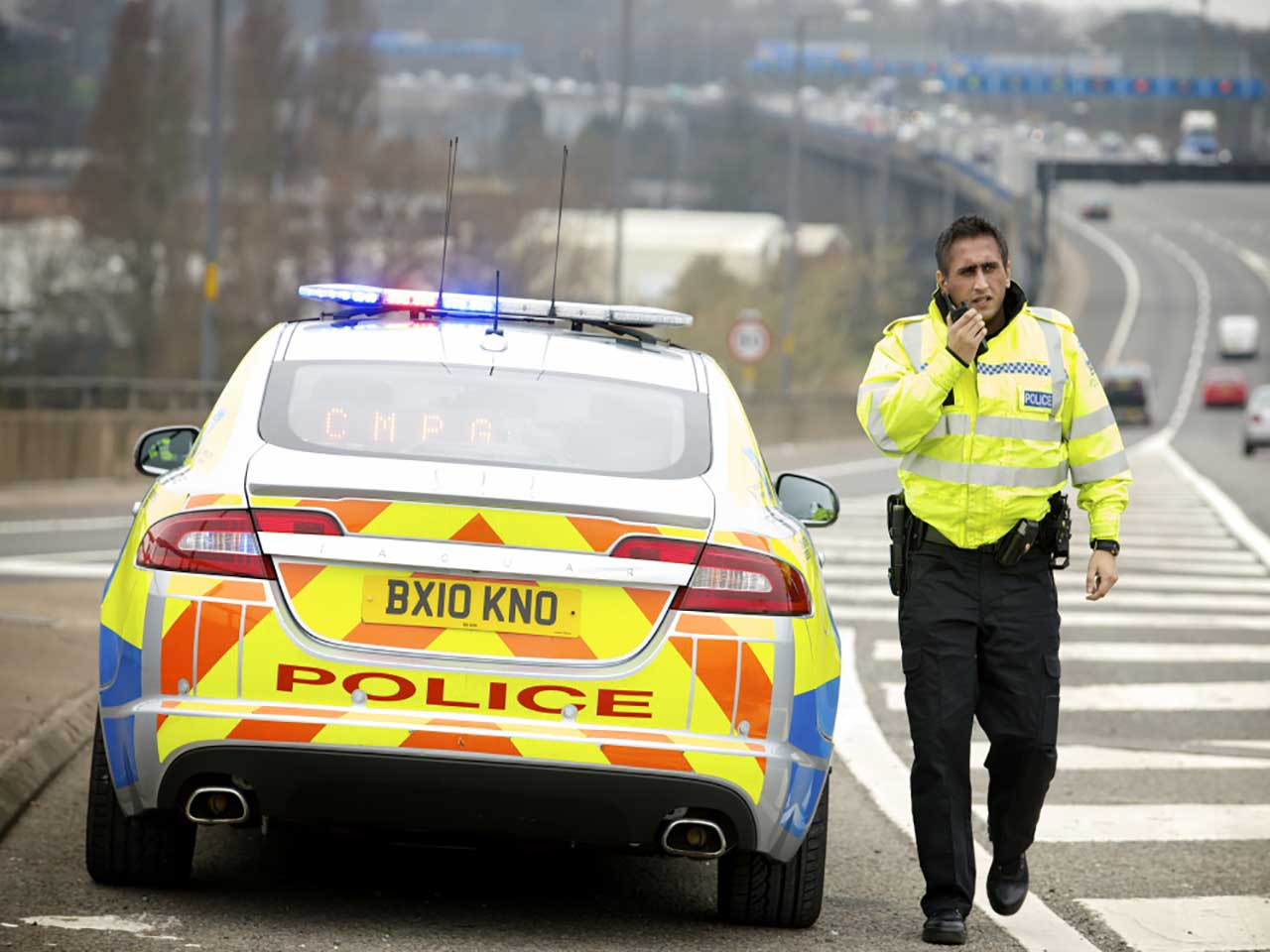 Traffic policeman stood next to his car on the motorway