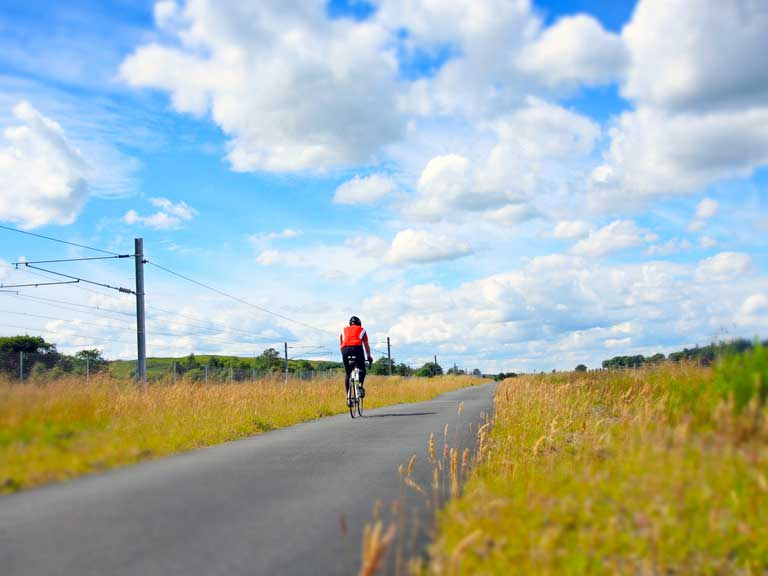 Cyclist riding along a country road.