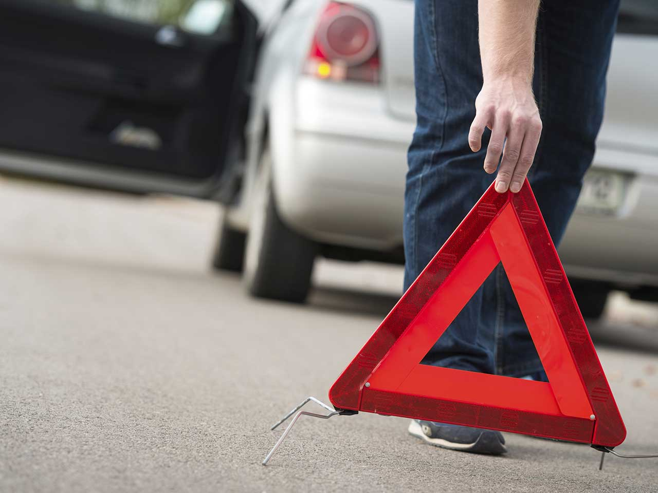 Scammer putting out a warning triangle to try to get motorists to pull over and help