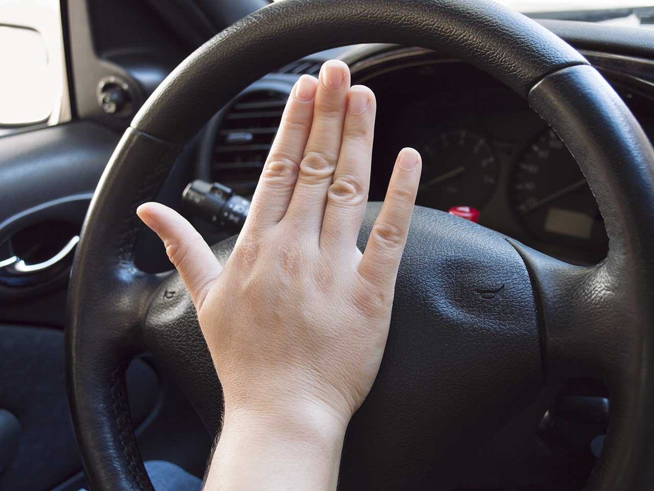 Driving slamming fist on the car horn to show frustration in an act of road rage