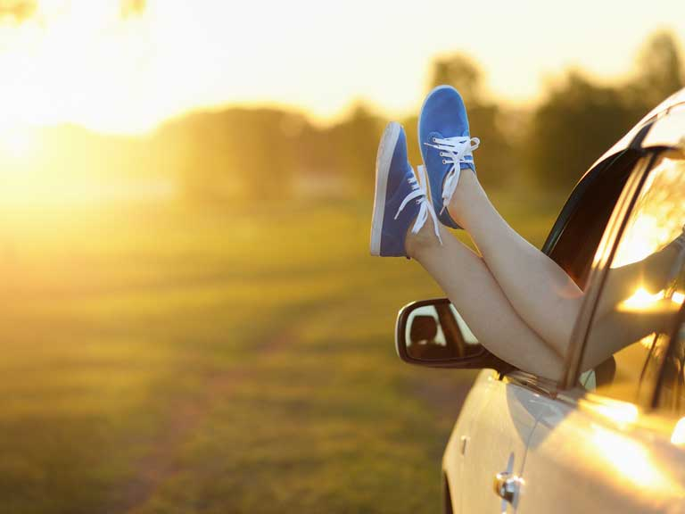 Parked car at sunset with the window wound down and feet resting on car door
