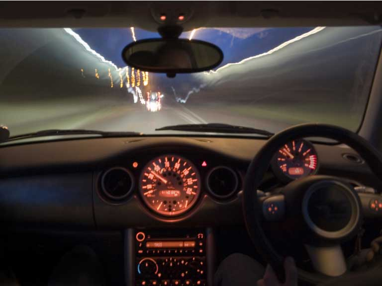 car interior including steering wheel driving at on road at night