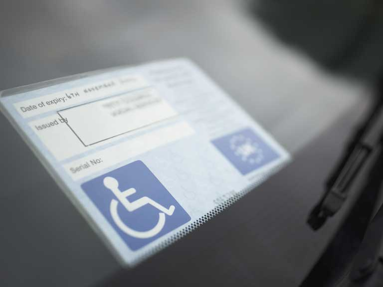 Disabled blue badge on display in a parked car