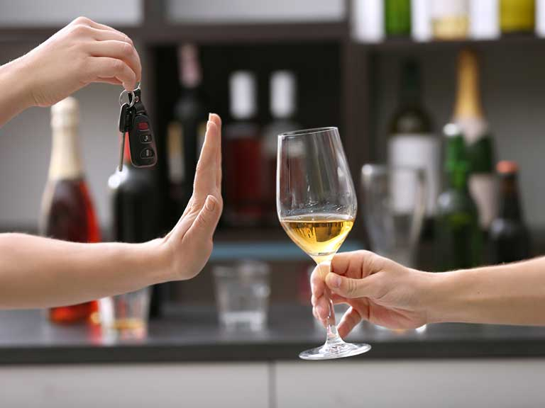 A woman refuses a glass of wine as she is driving