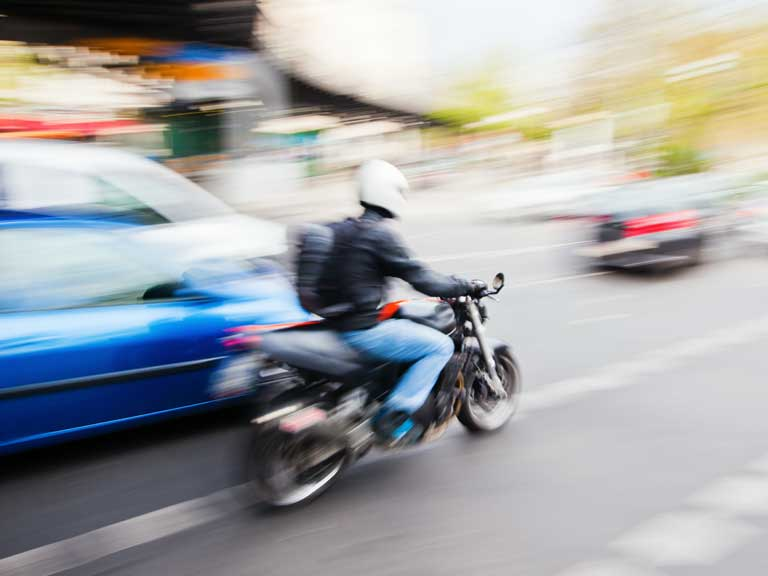 Motorcyclist on a motorbike overtaking a car that it is sharing the road with