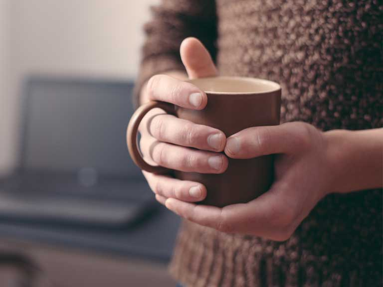 A bereaved person with comforting cup of coffee