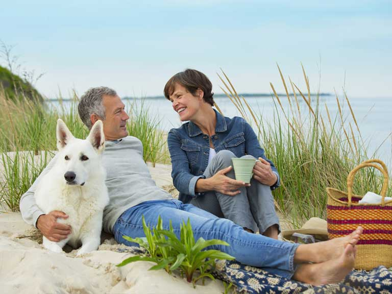 Mature couple with dog on beach