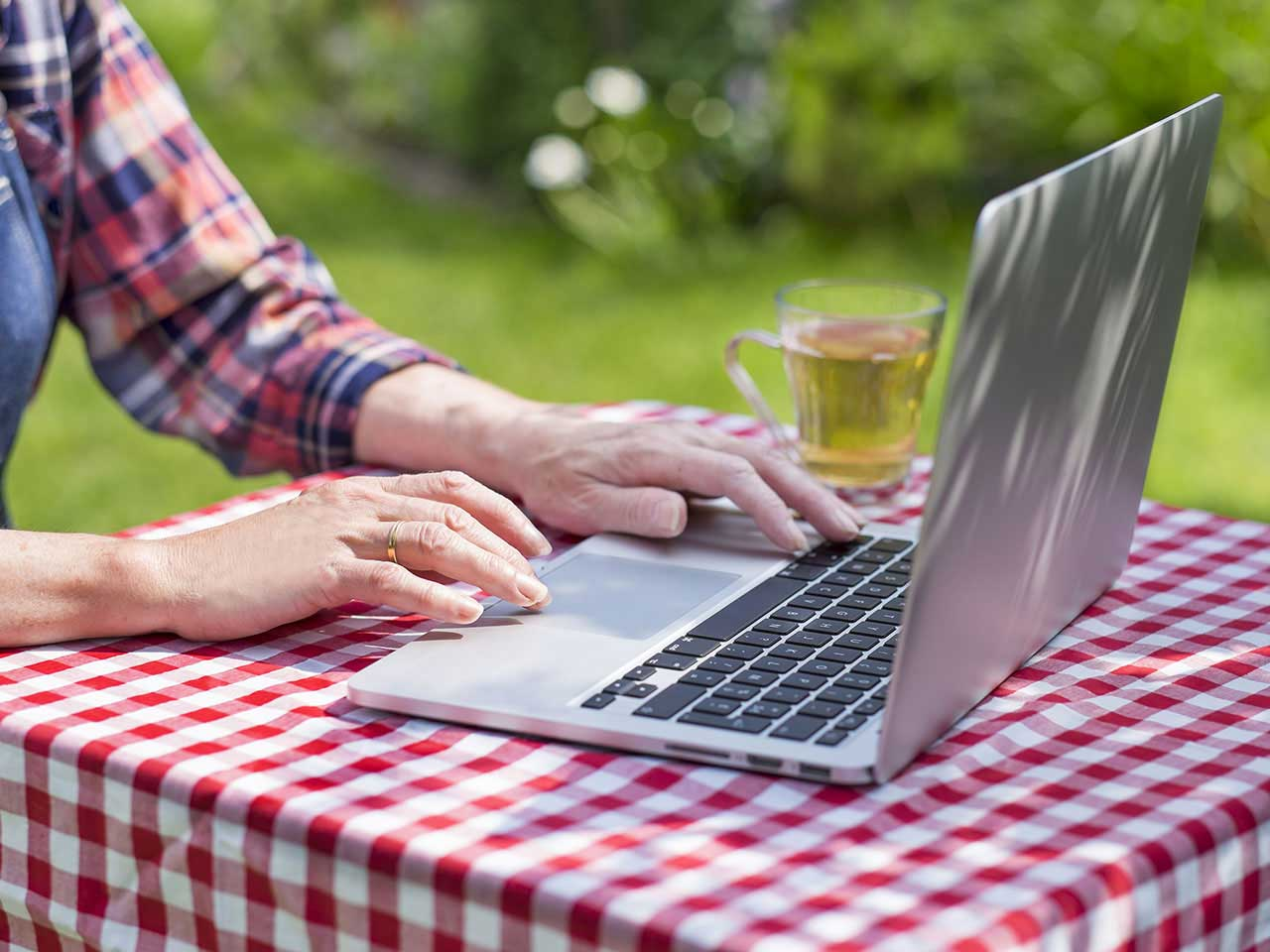 Mature lady using laptop in the garden