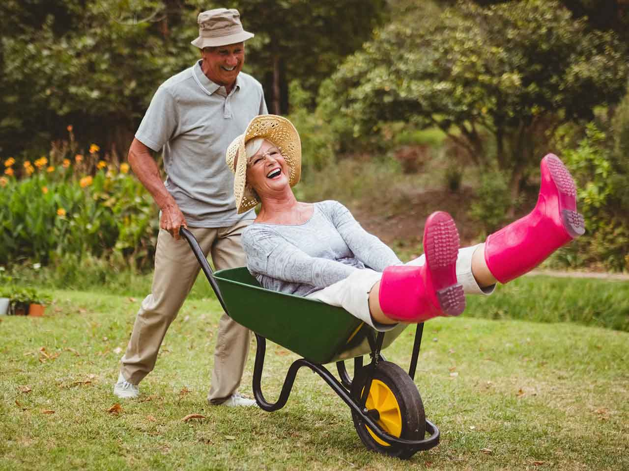 Senior man pushing mature lady in wheelbarrow
