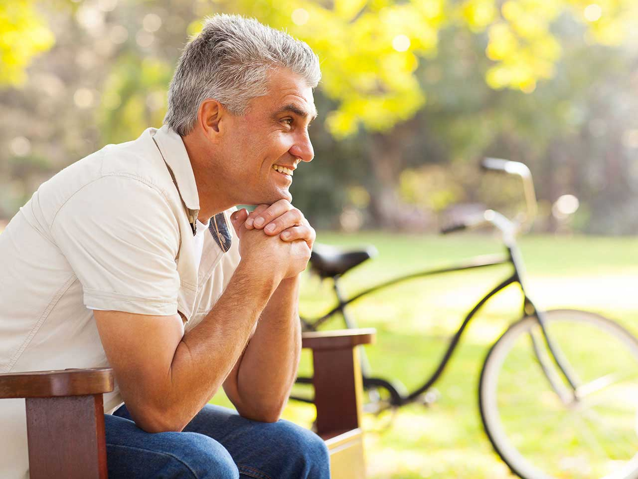 Mature man sitting on a bench smiling