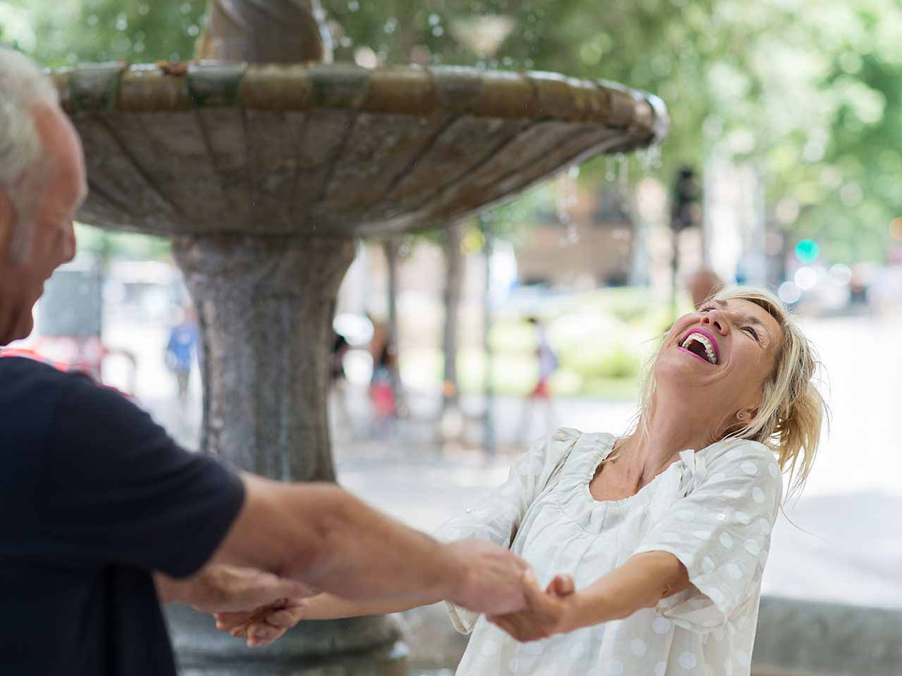 Happy mature couple embracing by a fountain