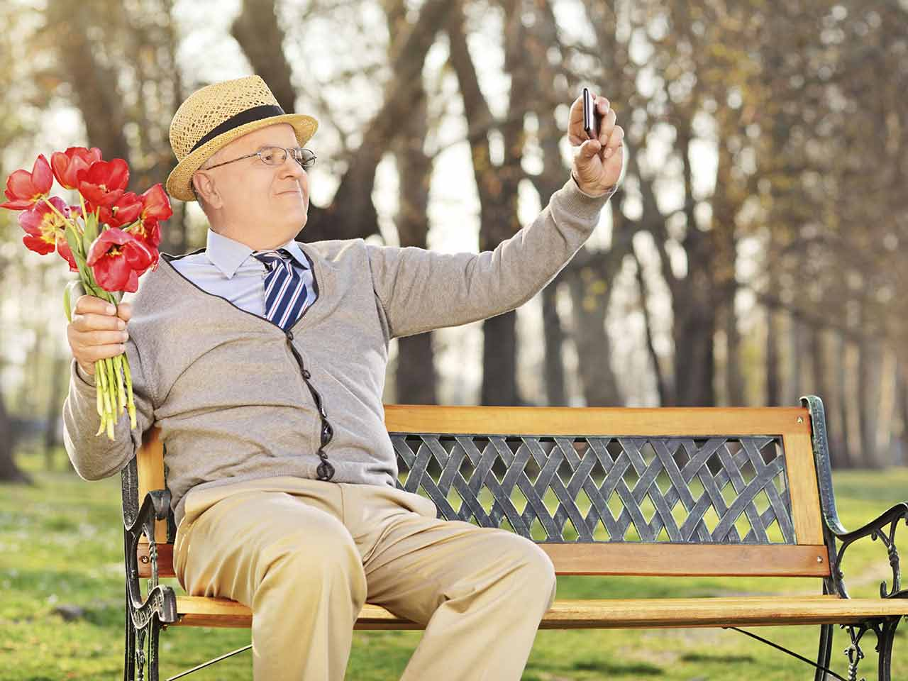 Senior gentleman sitting on bench with flowers wiating for a date