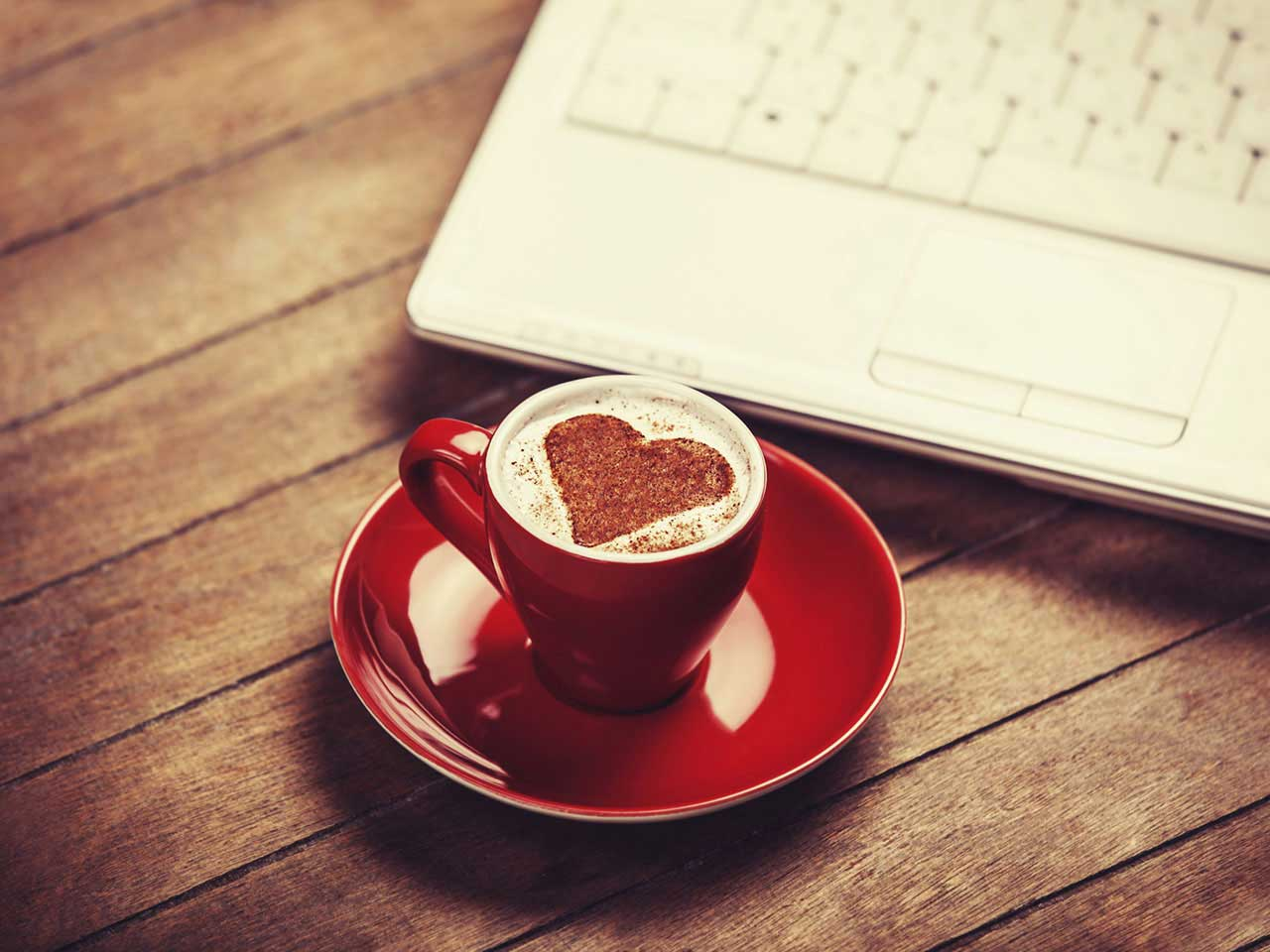 Laptop and coffee cup with heart symbol symbolising online dating