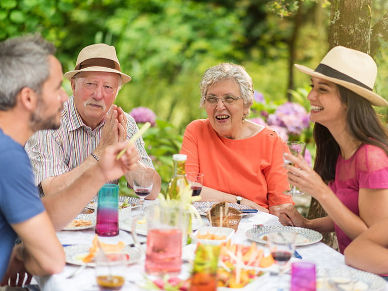 A happy multi-generational family enjoy a meal because they aren't discussing politics