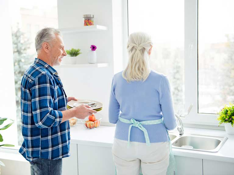 An older couple do the washing up