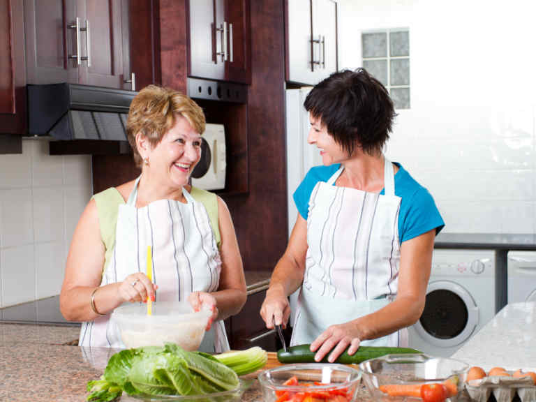 A mother and daughter cook together in the kitchen