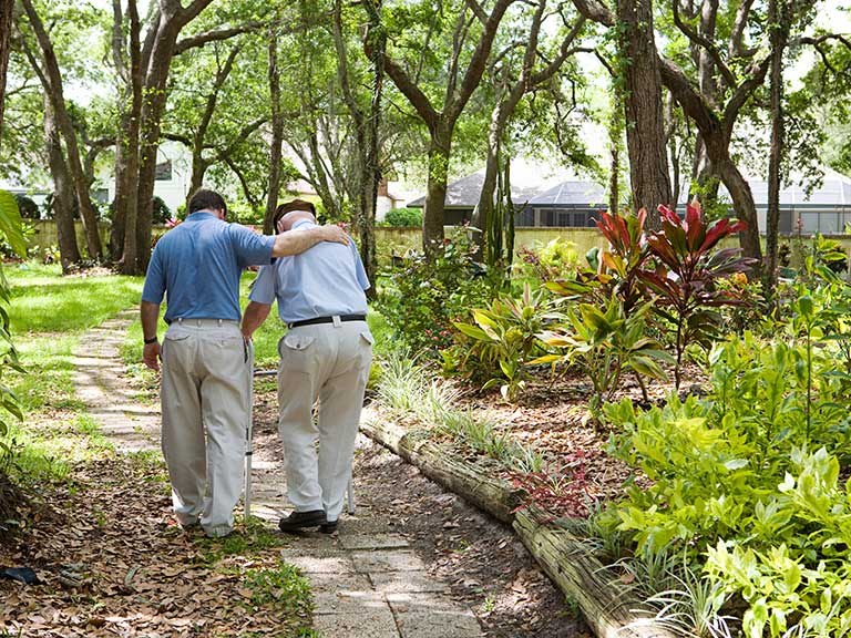 A son and his father walk through the grounds of a care home