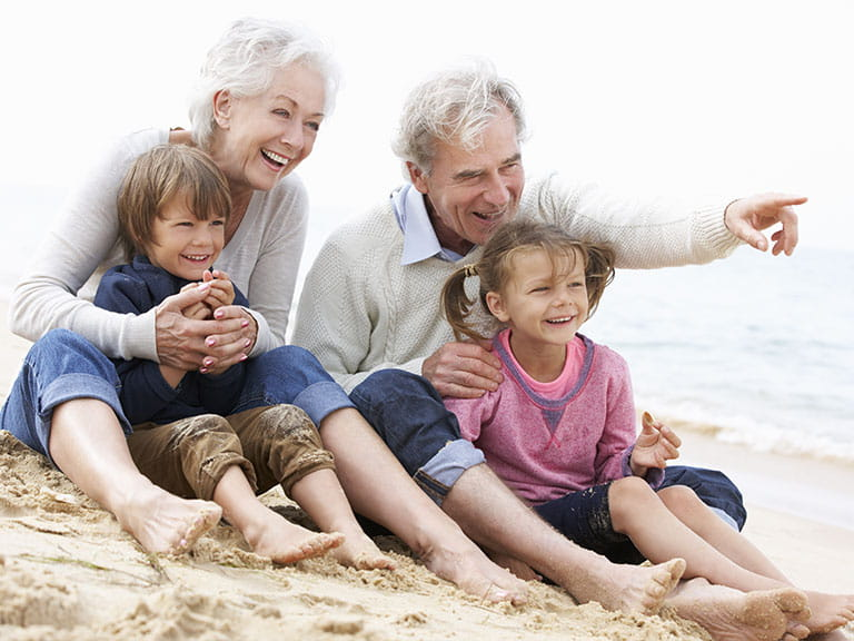 An older couple enjoy a day on the beach with two foster children
