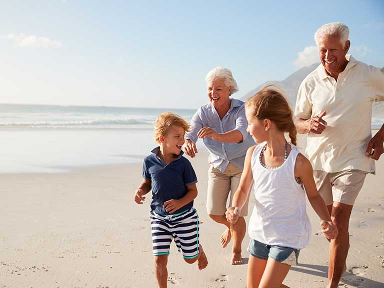 Grandparents run on the beach with grandchildren