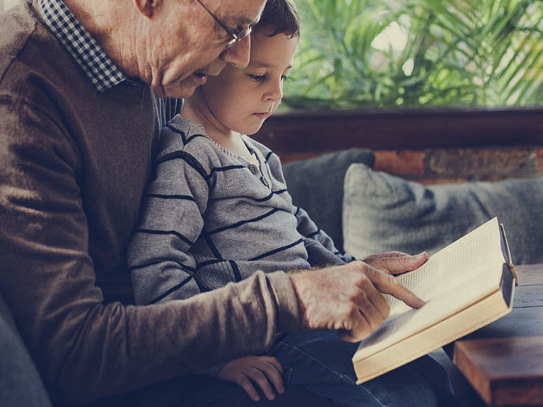 A grandfather and grandson read together