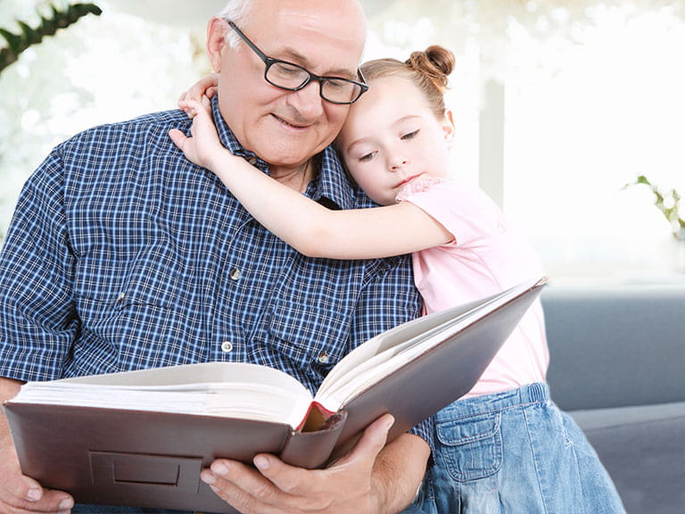 A grandfather reads a book with his granddaughter