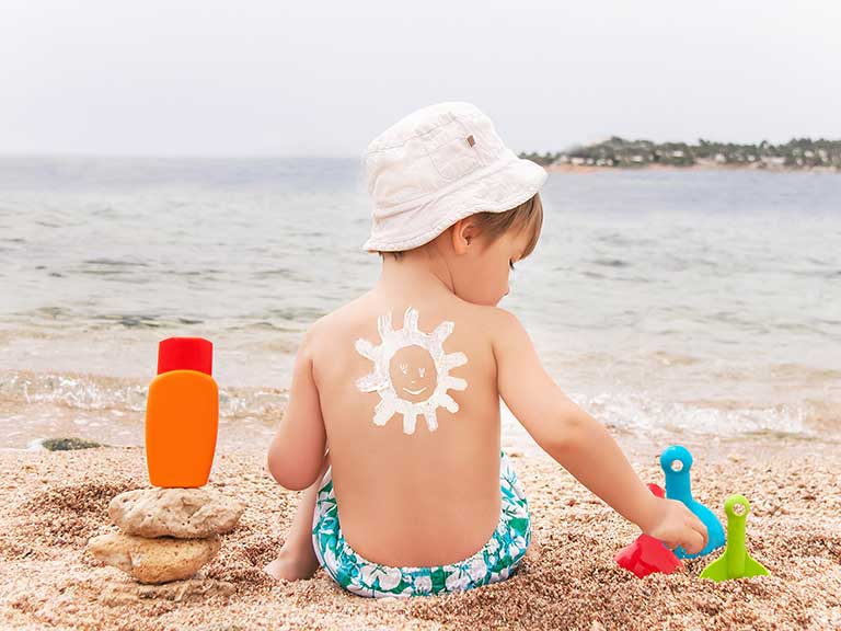 A small child sits on the beach in the sun with suntan lotion on