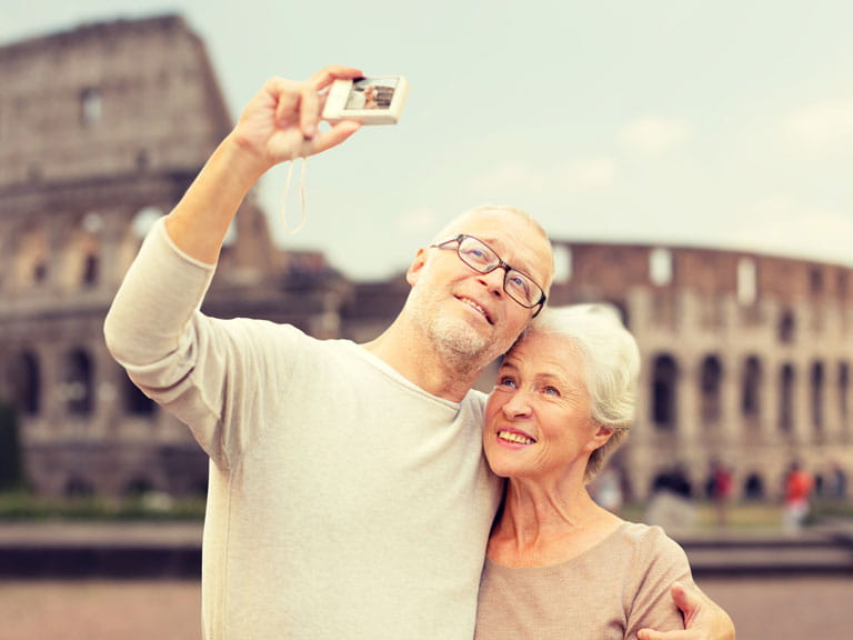 An older couple take a selfie outside the Colusseum