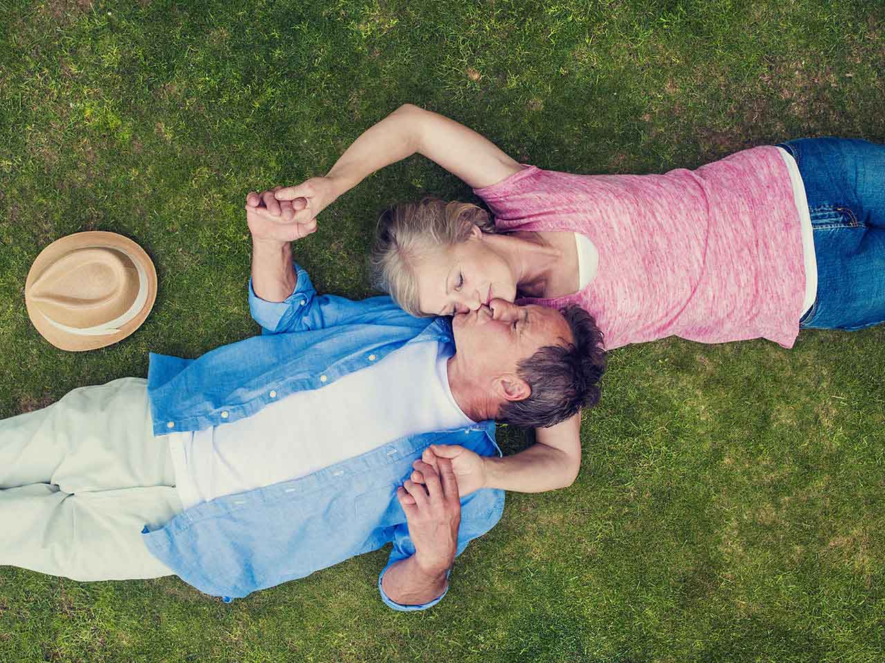 Mature couple lying on the grass embracing