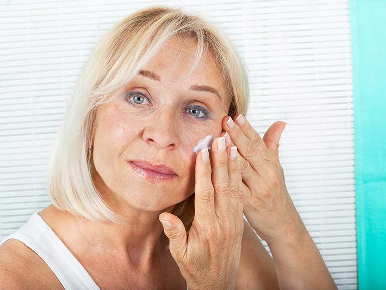 An older lady applies cream to moisturise her face