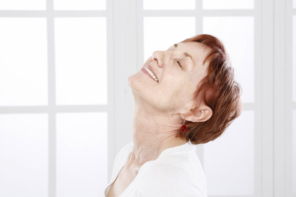 Older woman laughing, showing her neck