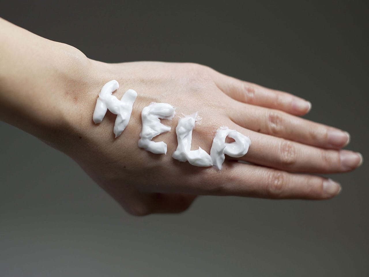 Ageing hand with help written on it in handcream