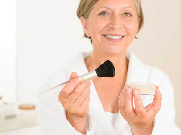 An older lady prepares to put powder on to contour her face