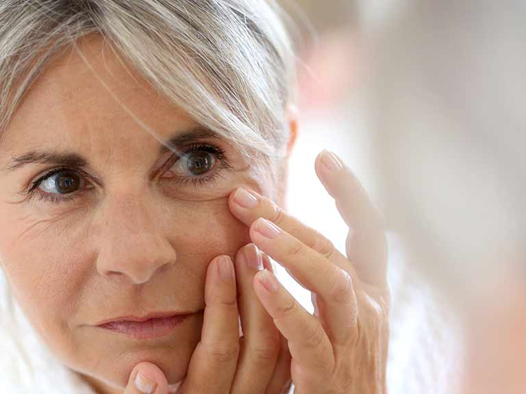 A beautiful older lady applies eye cream to help with crows feet