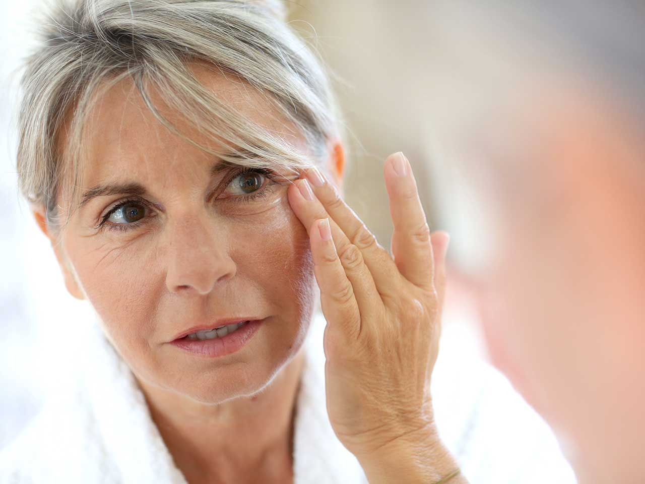 Mature woman applying moisturiser