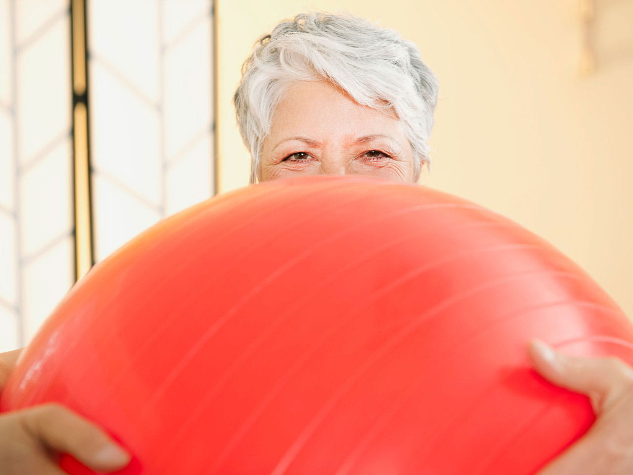 Grey haired lady holding gym ball with smiley eyes