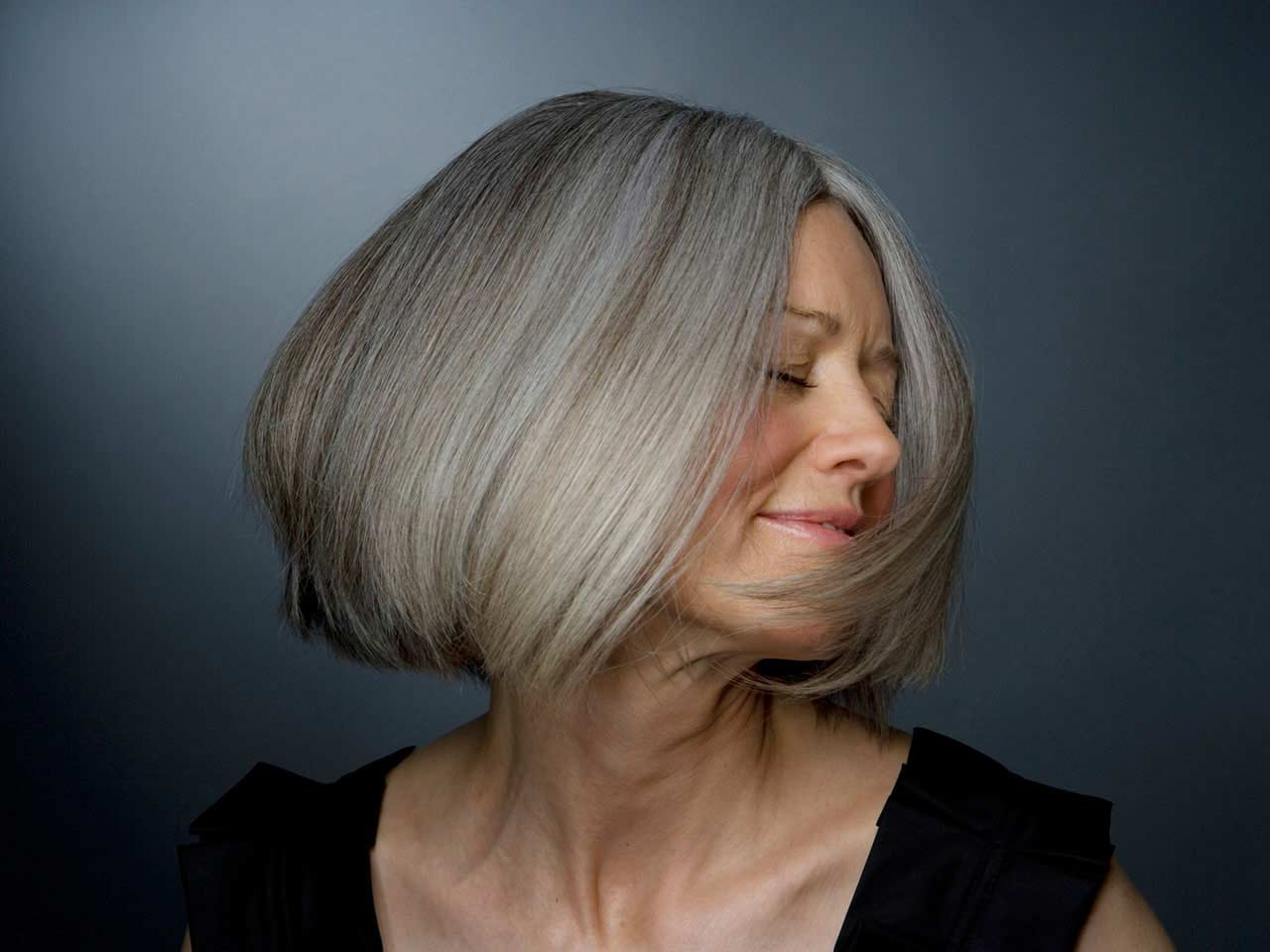 Mature lady with a grey bob swinging her hair
