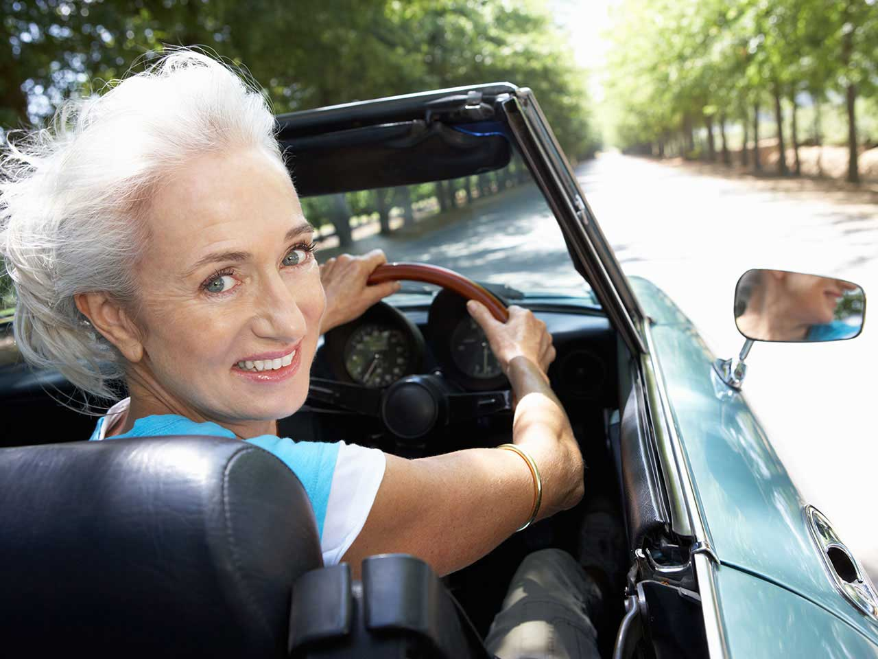 Senior lady driving sports car in the summer