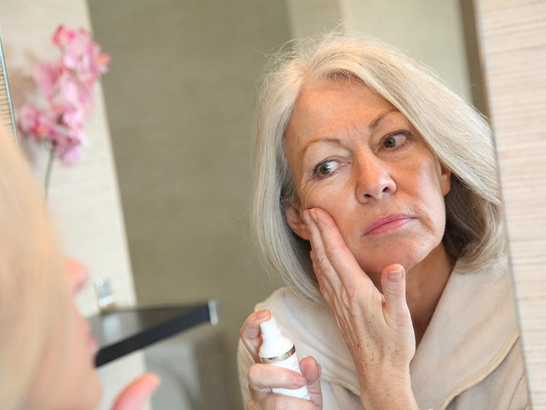 Senior woman applying moisturiser