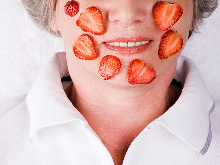 An older woman has strawberries on her face to symbolise the red hues of rosacea