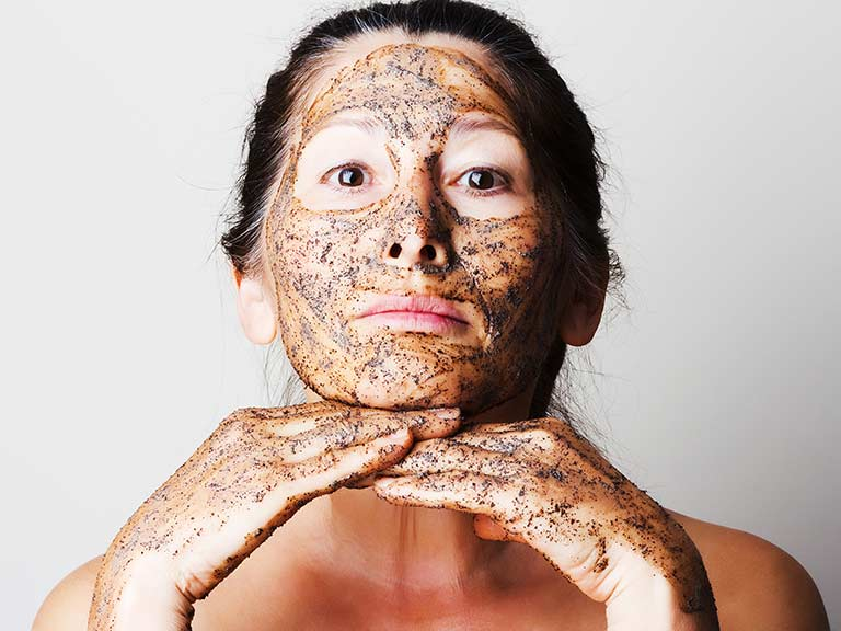 An older lady uses a homemade coffee scrub to exfoliate instead of harmful microbeads
