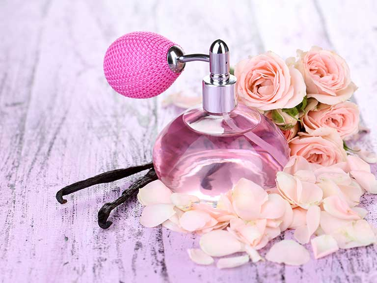 Pretty pink perfume bottle surrounded by flowers